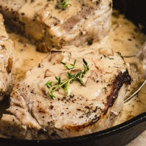 Apple Cider Brined Pork Chops in a creamy apple cider sauce in an iron skillet.