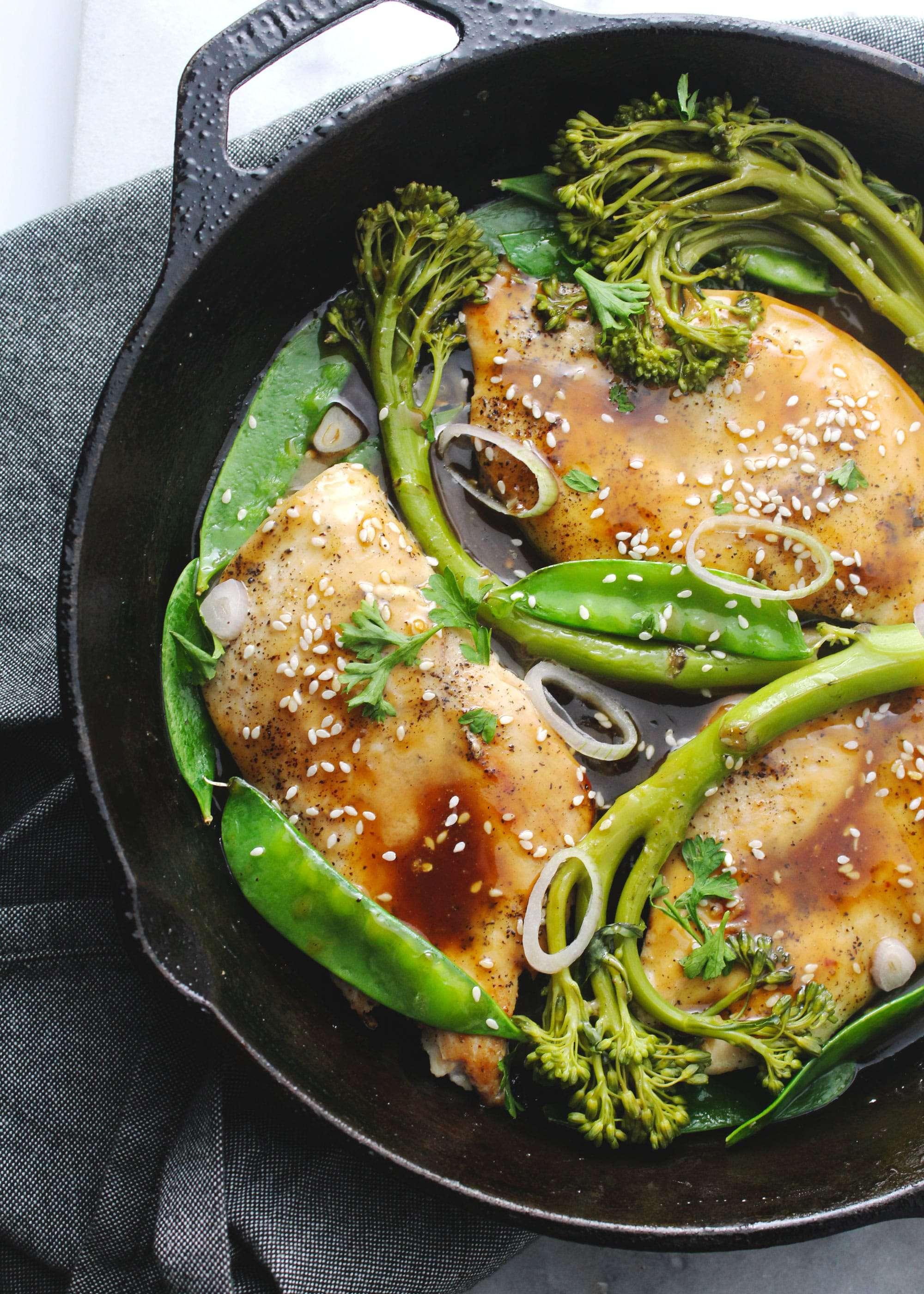 Sesame honey glazed chicken with broccolini in a black skillet.