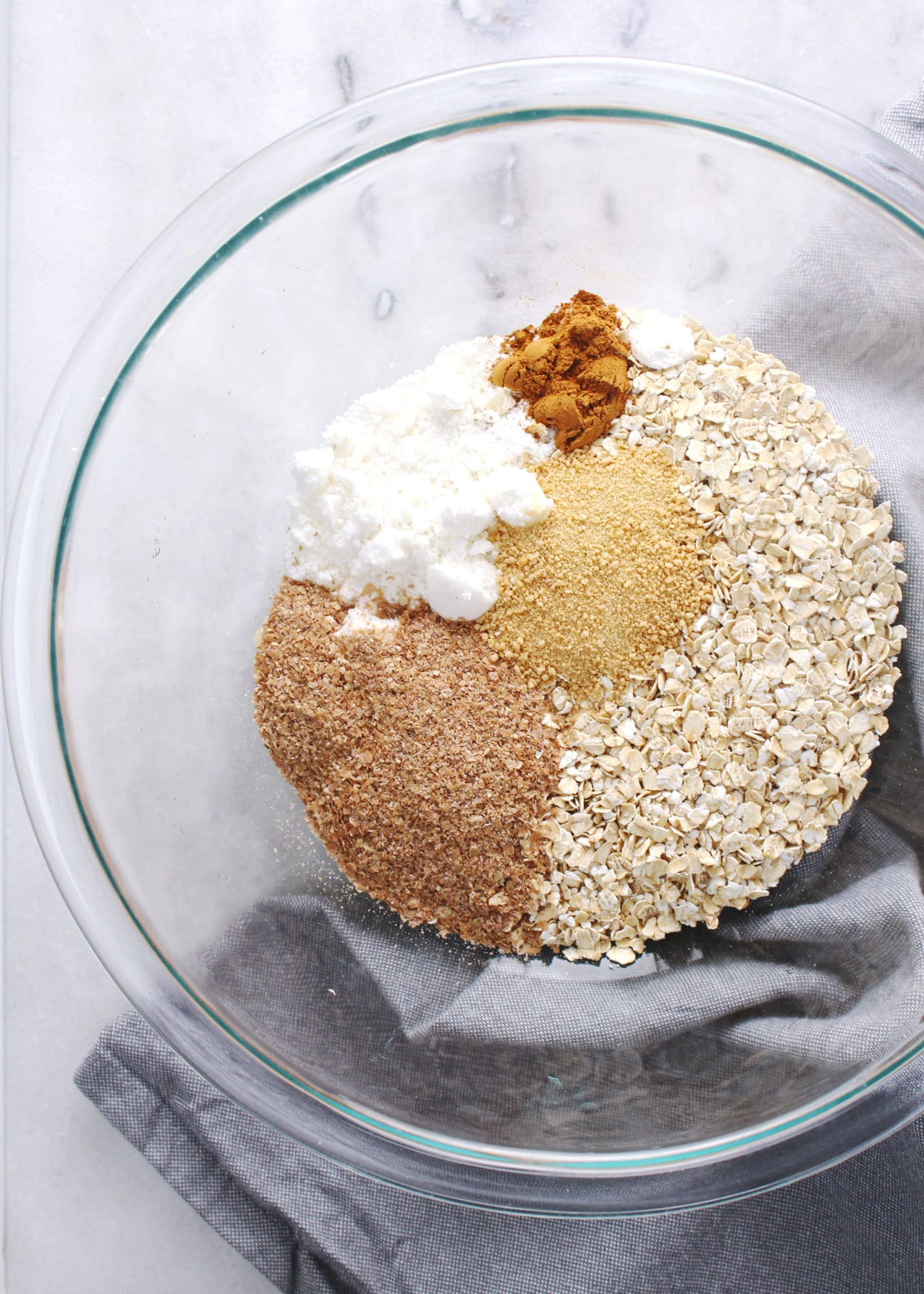 ingredients for making instant oatmeal packets in large glass bowl