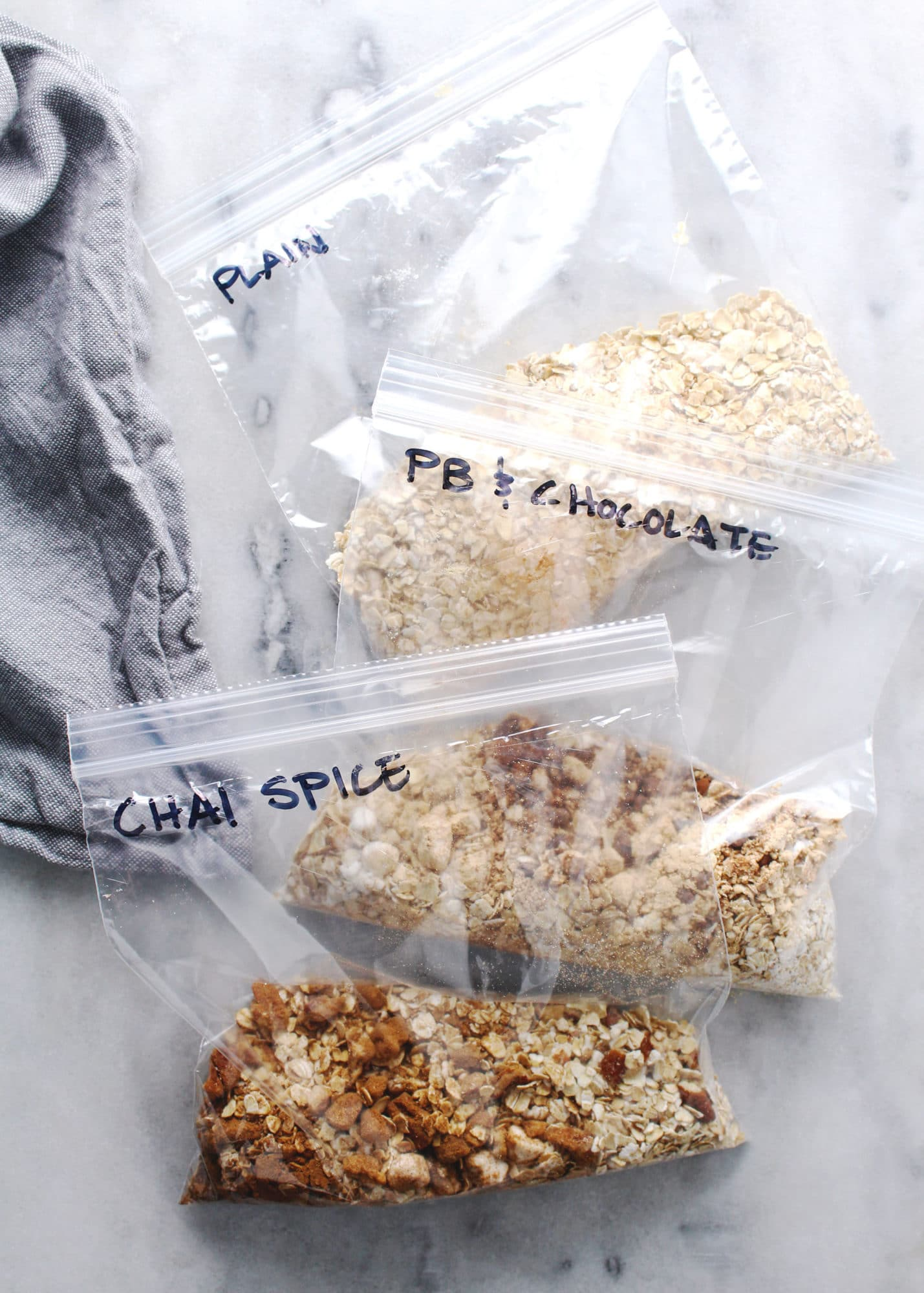 flavored homemade instant oatmeal packets in zip-top bags on marble table