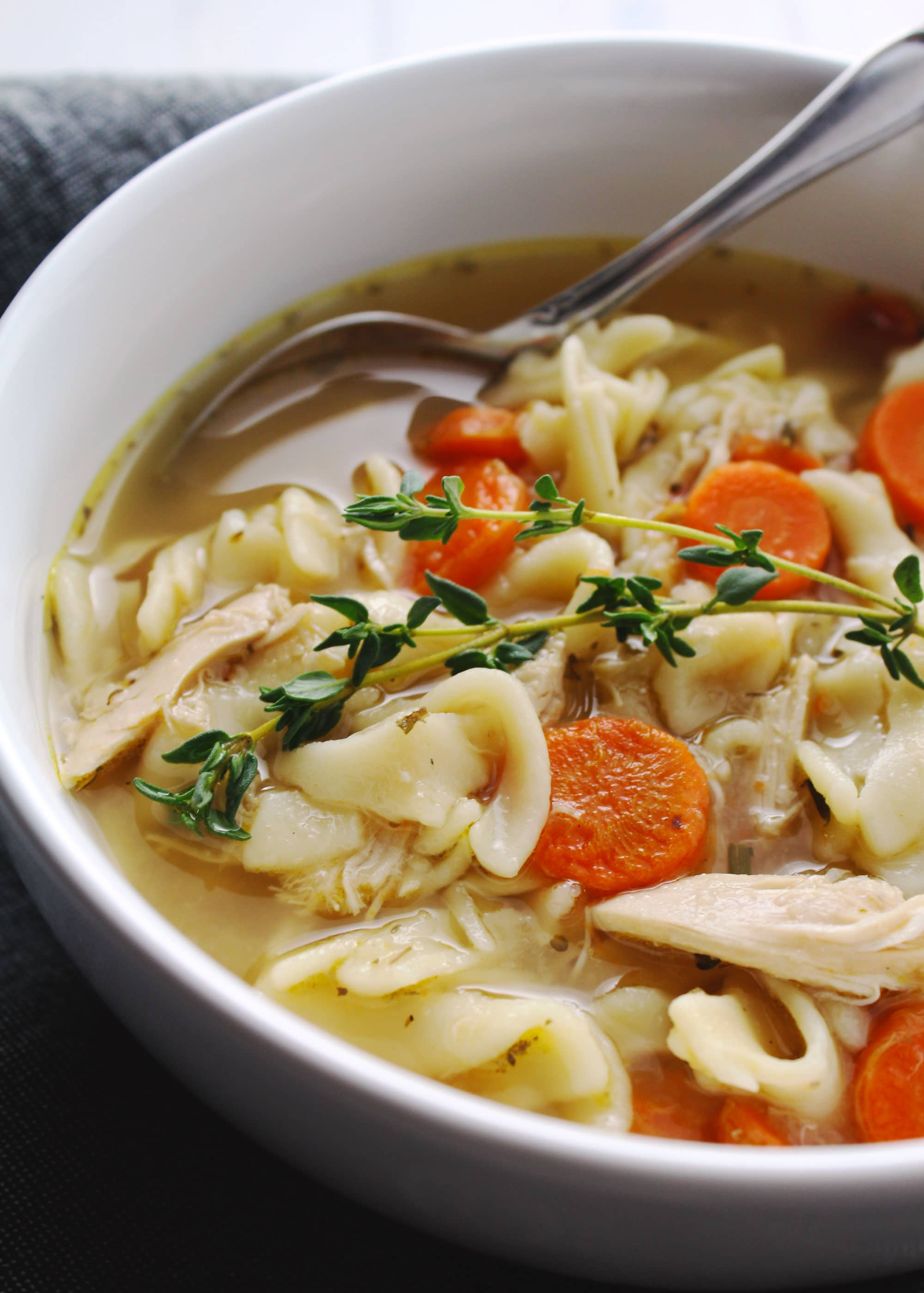Homemade chicken noodle soup topped with thyme in a white bowl.