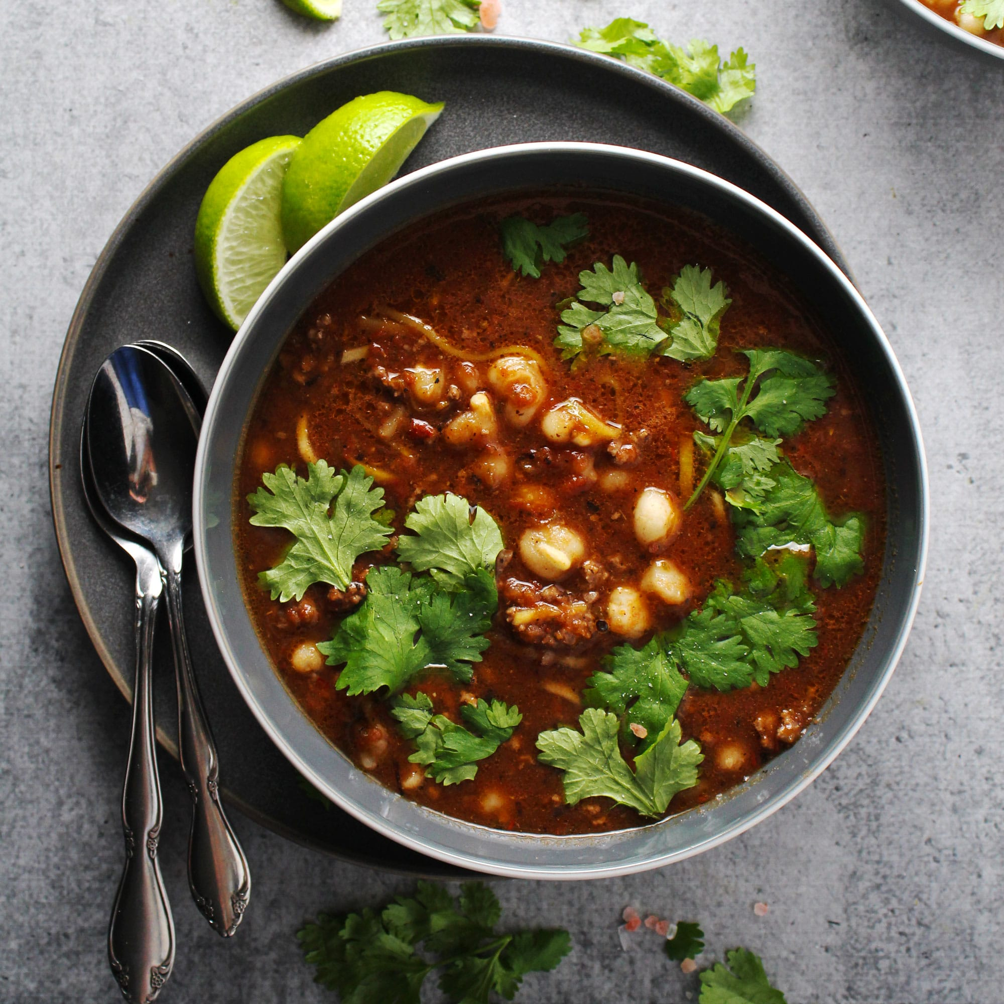 Picture of pozole rojo stew in gray bowl.