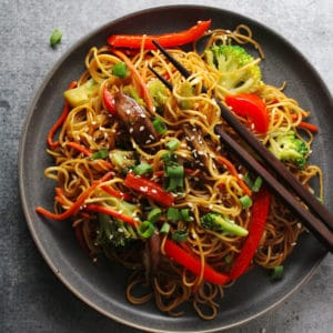 Vegetable lo mein on a black plate with brown chopsticks.