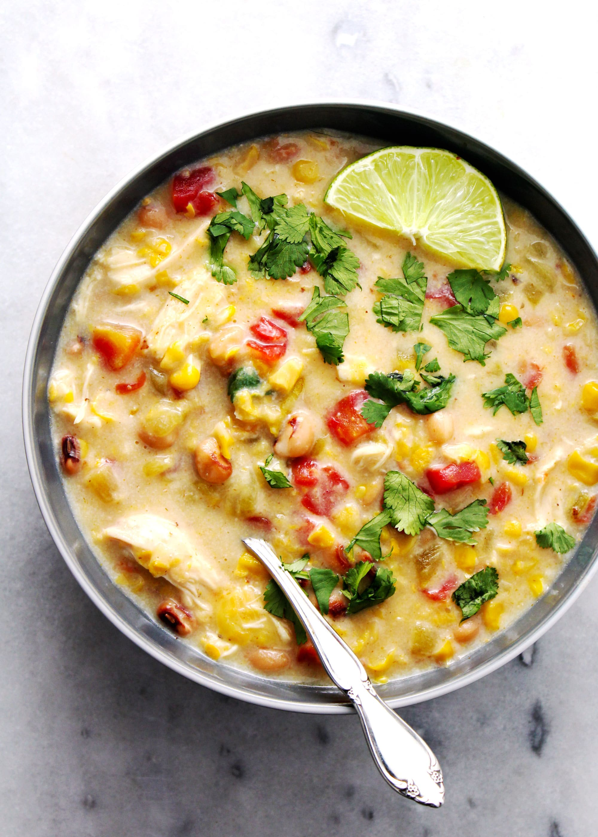 Black-eyed pea and corn chowder in a gray bowl with lime wedges.
