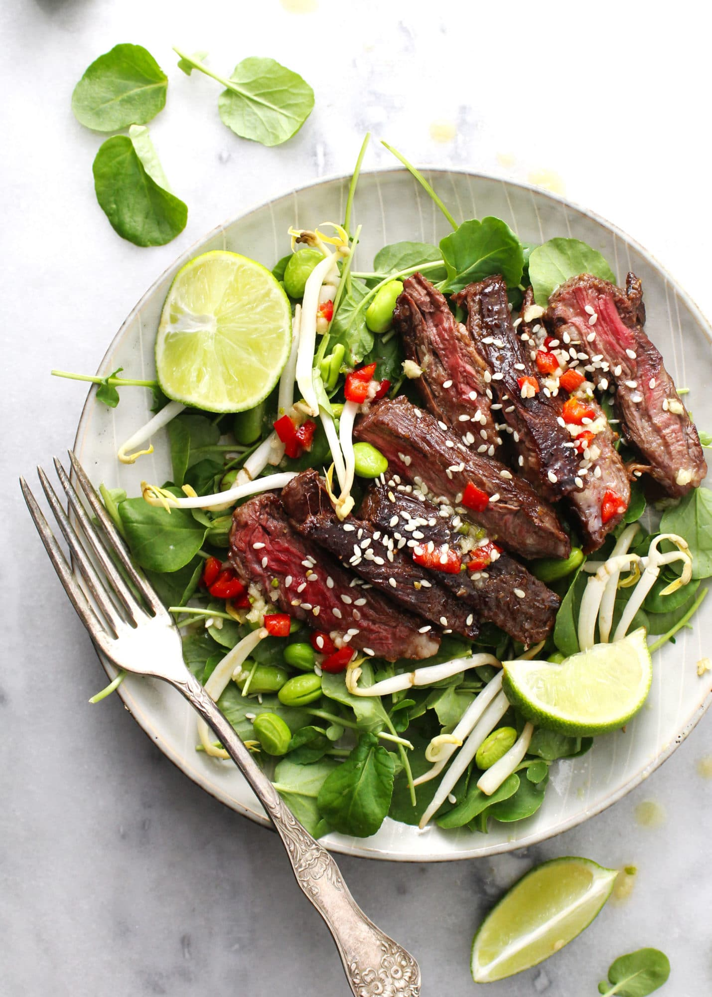 korean bbq steak salad with lime wedges on gray plate