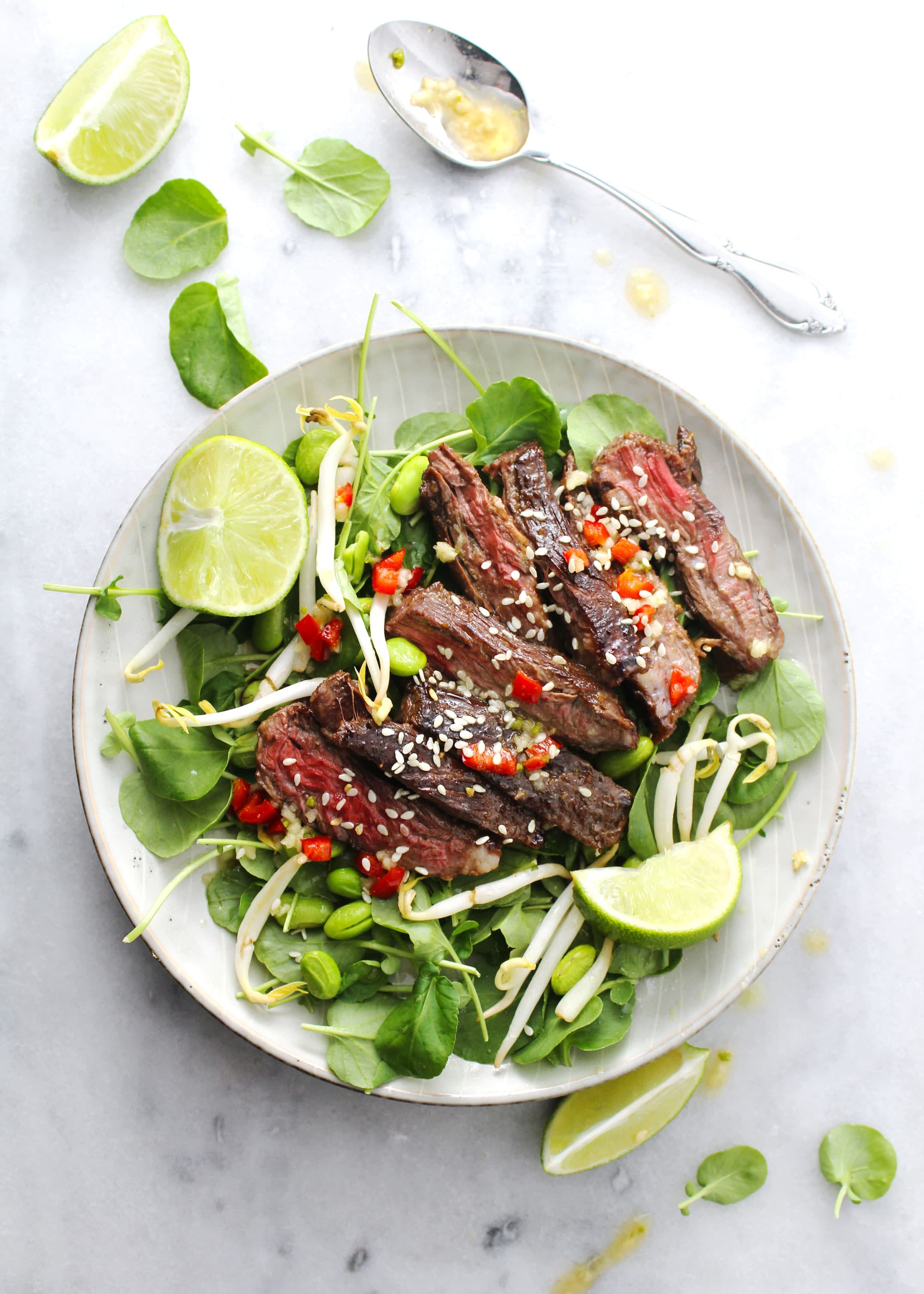 Korean BBQ steak salad with lime wedges on the side on a round plate.