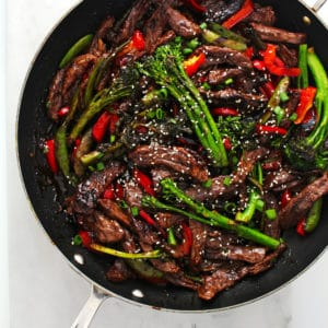 Beef stir fry tossed with vegetables in a large black skillet and topped with sesame seeds.