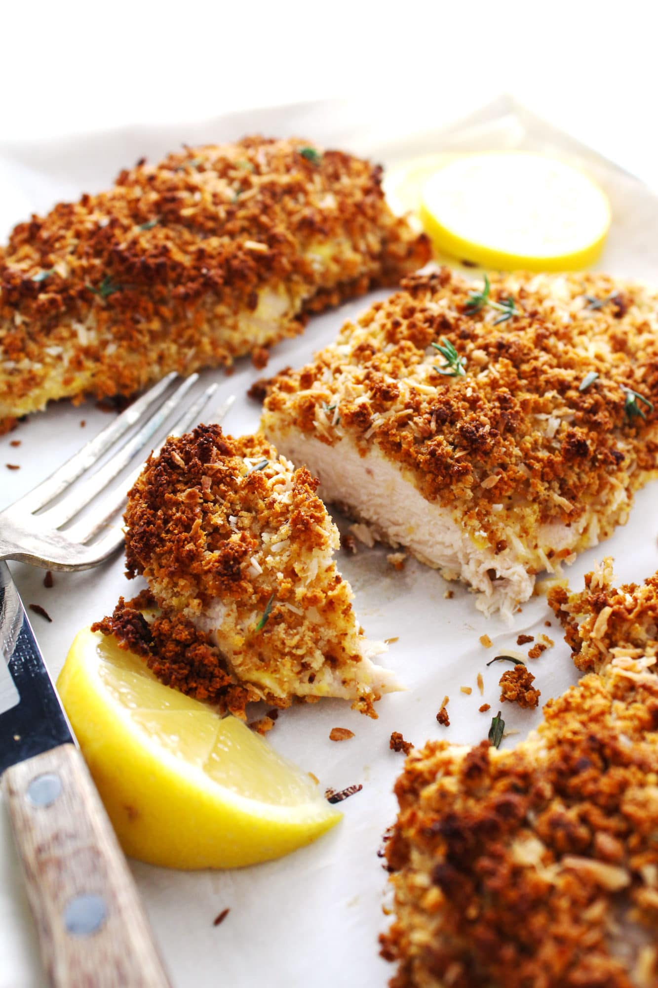 gluten-free breaded coconut chicken sliced in half with lemon wedge and sliver fork