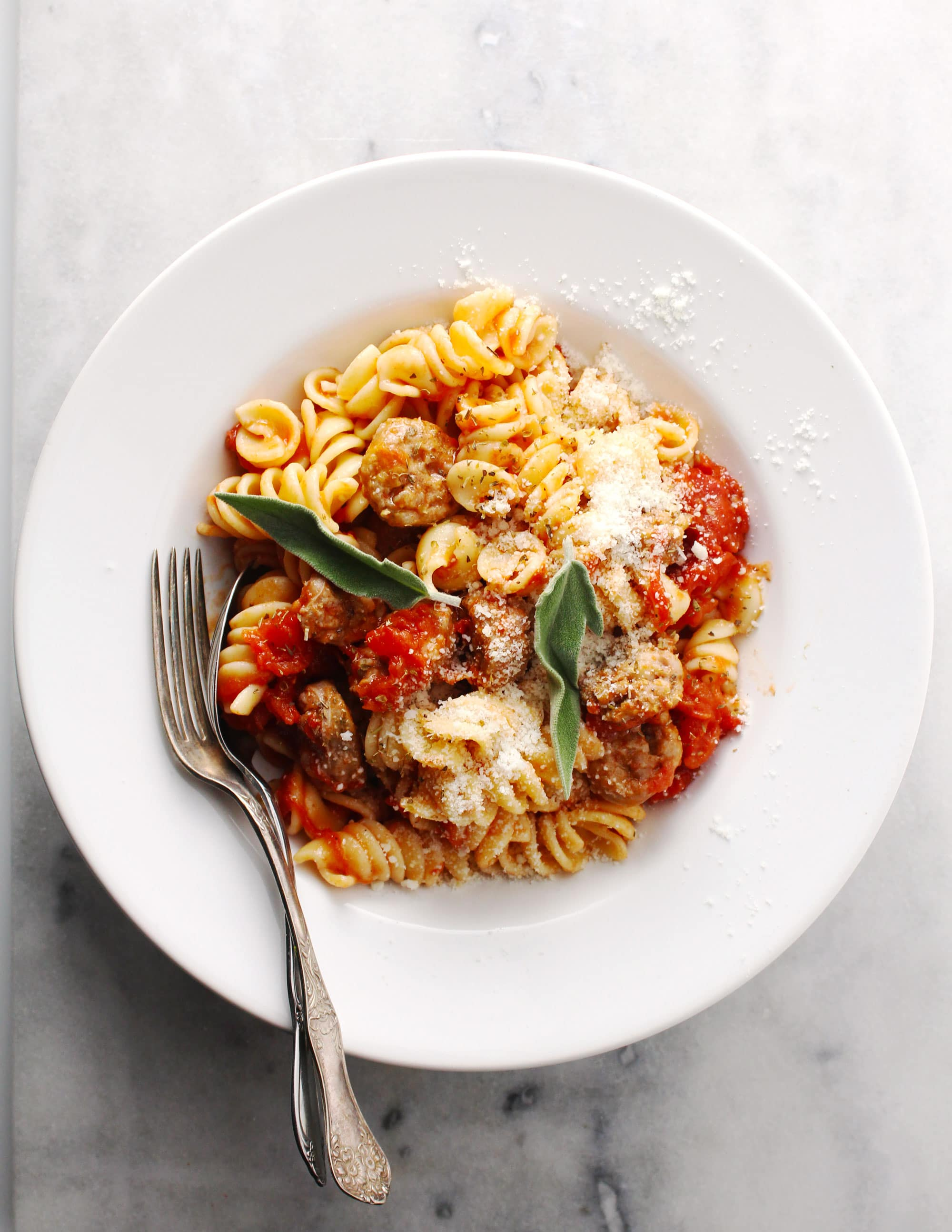 Sausage Pasta Pomodoro in a white bowl with two forks.