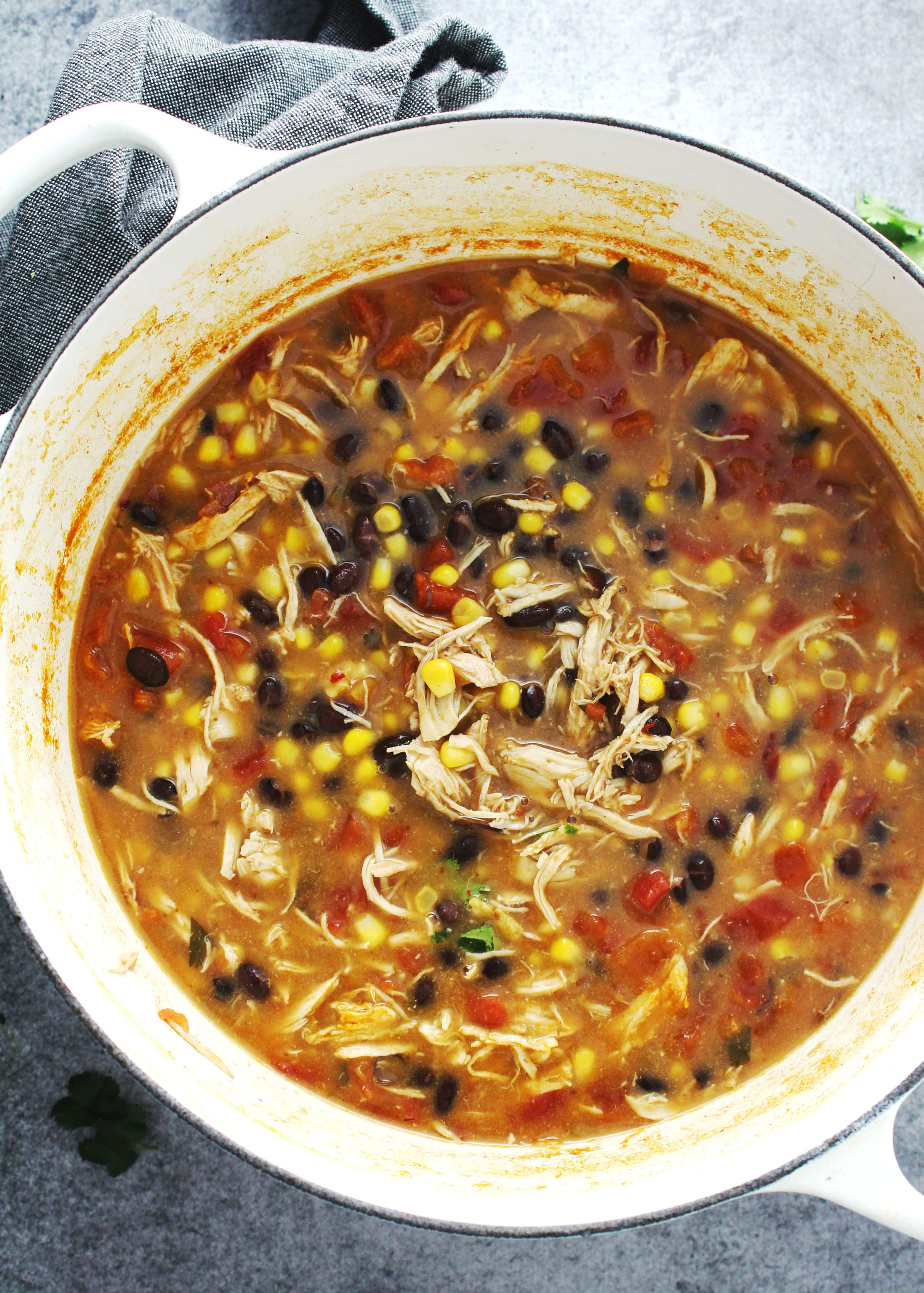 Chicken tortilla soup in a large white pot.