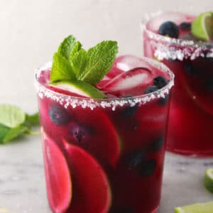 Blueberry mint margarita topped with fresh mint leaves.