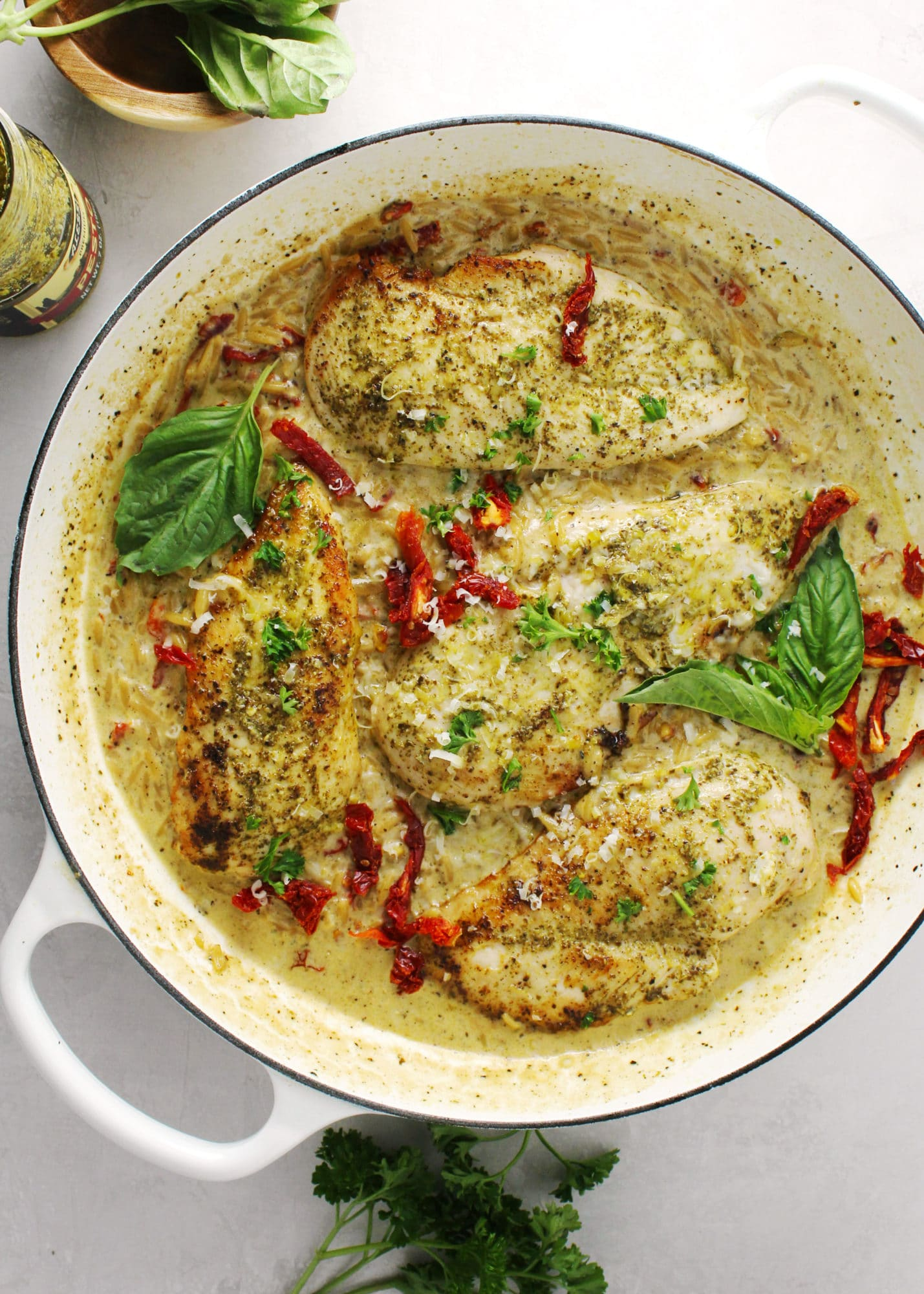 Creamy basil pesto chicken topped with fresh basil leaves in a white skillet.