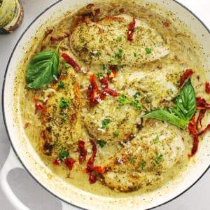 Creamy basil pesto chicken in a white skillet.