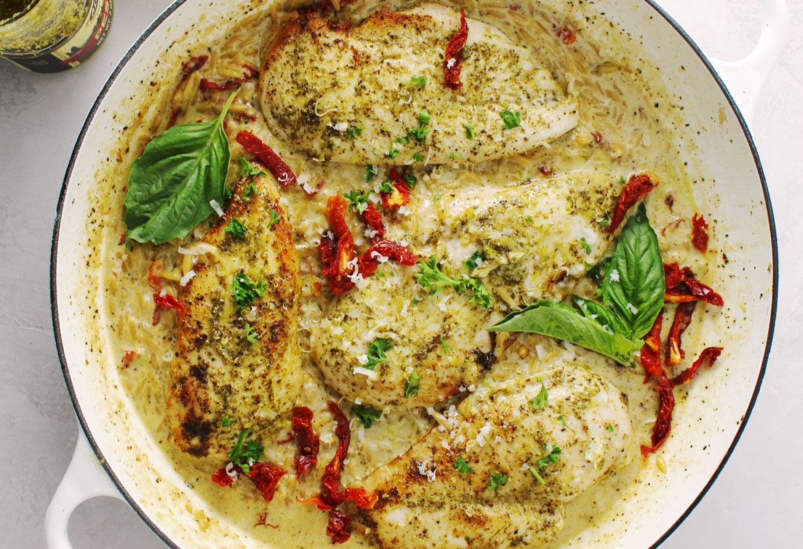 Creamy Basil Pesto Chicken topped with sun-dried tomatoes and basil leaf.