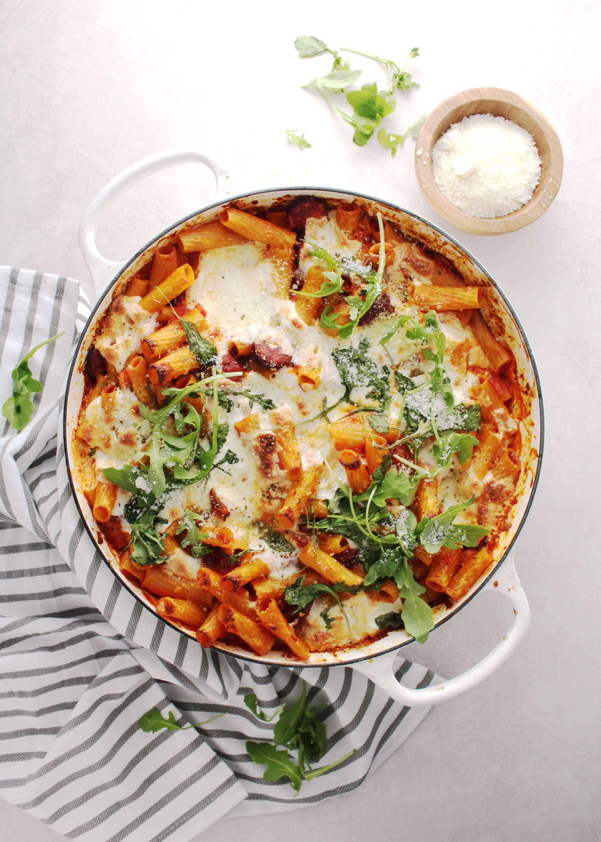 Baked rigatoni with red peppers and topped with fresh thyme in a white skillet.