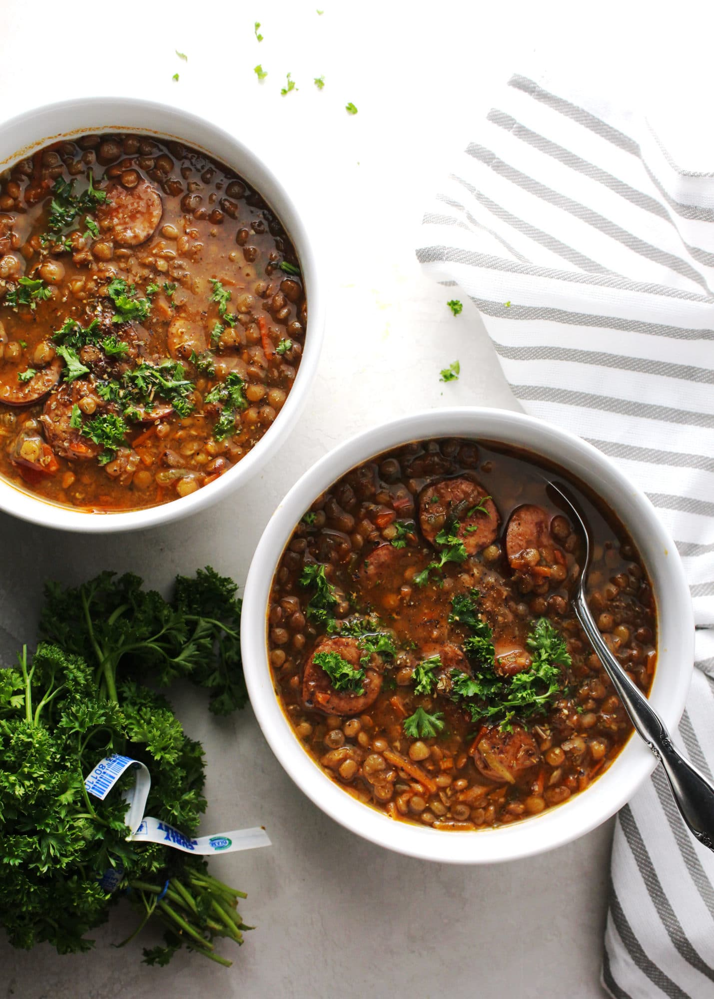 lentil stew with sausage in white bowls with silver spoon