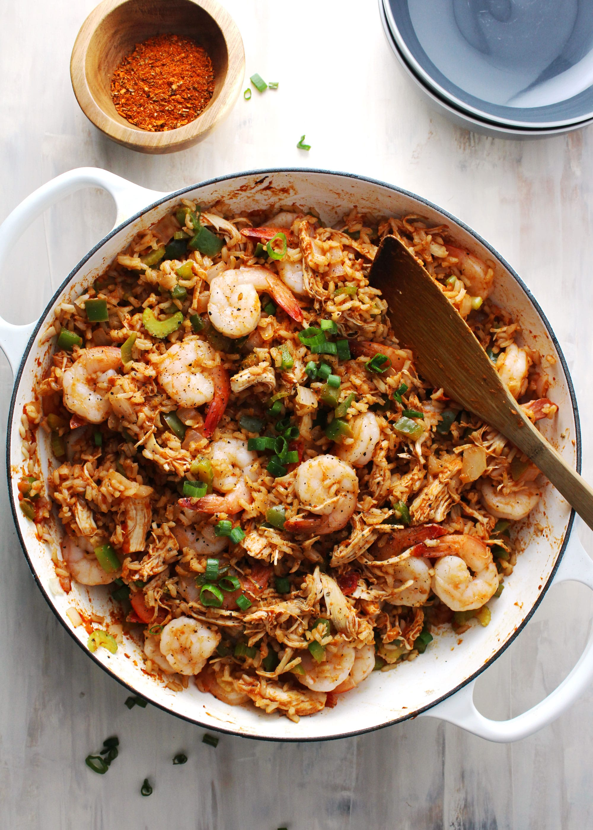 jambalaya in a white skillet with wooden spoon
