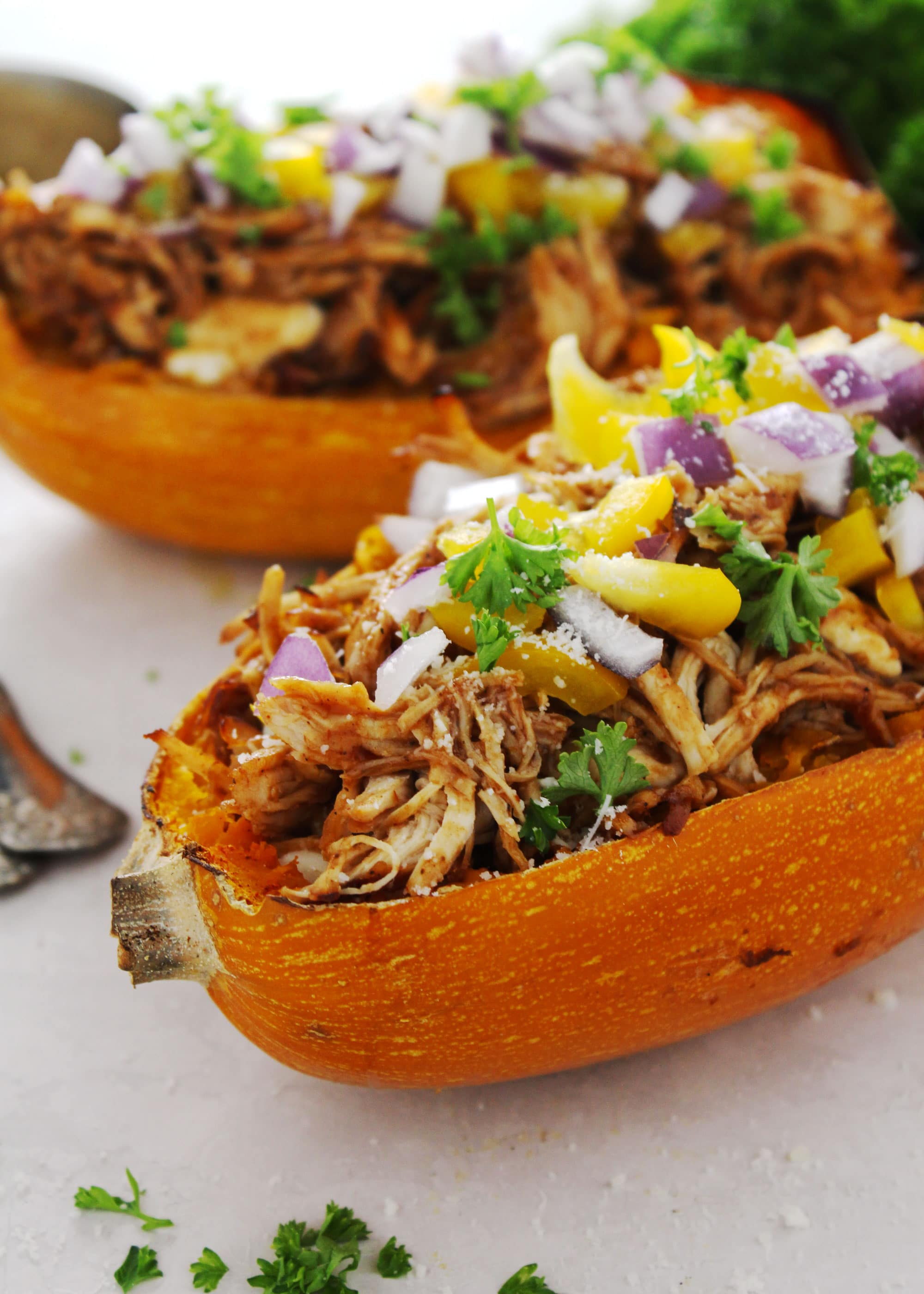 Spaghetti squash stuffed with barbecue pulled chicken and topped with delicious vegetables.