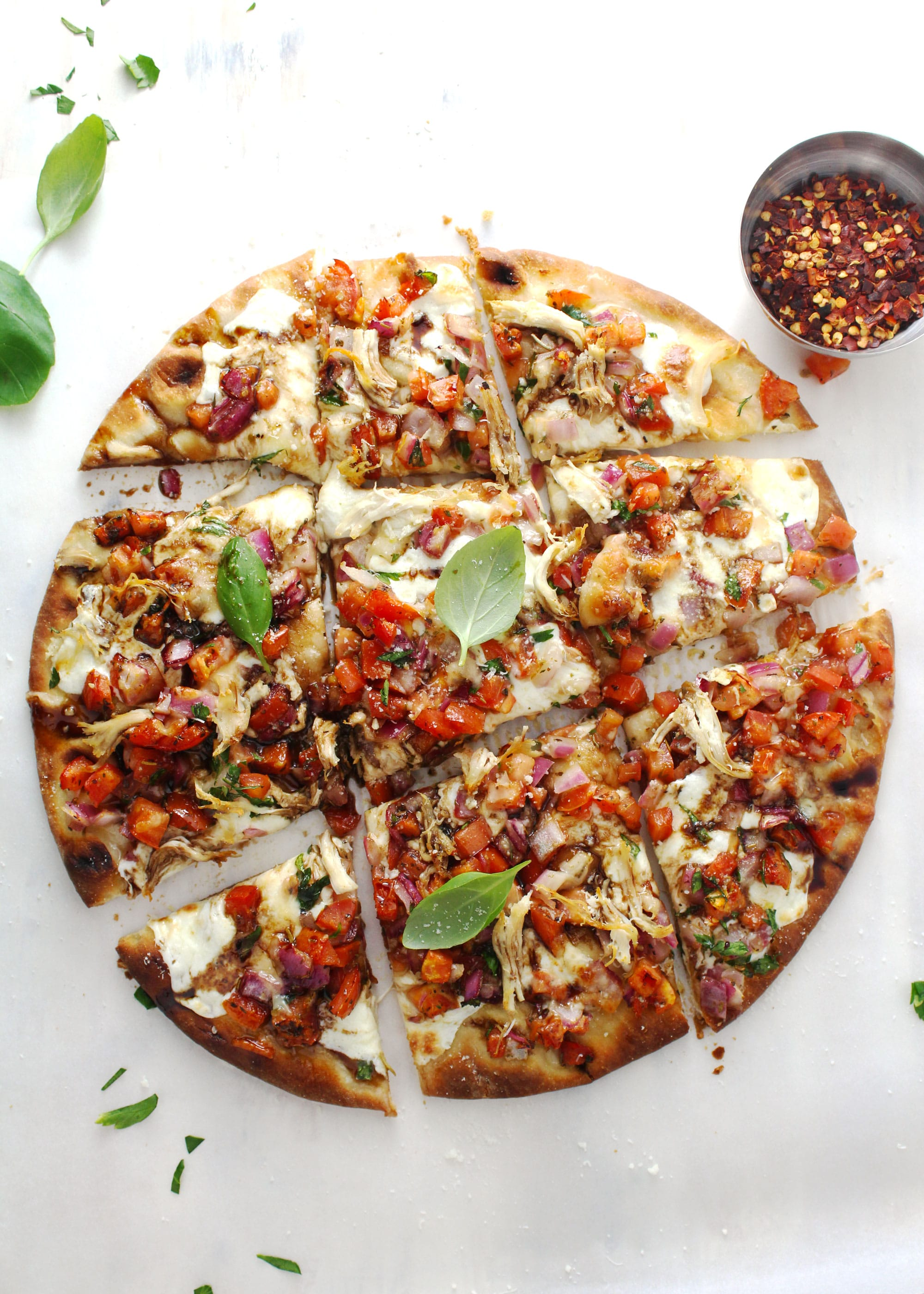 Bruschetta pizza topped with chicken and basil leave on a white surface.