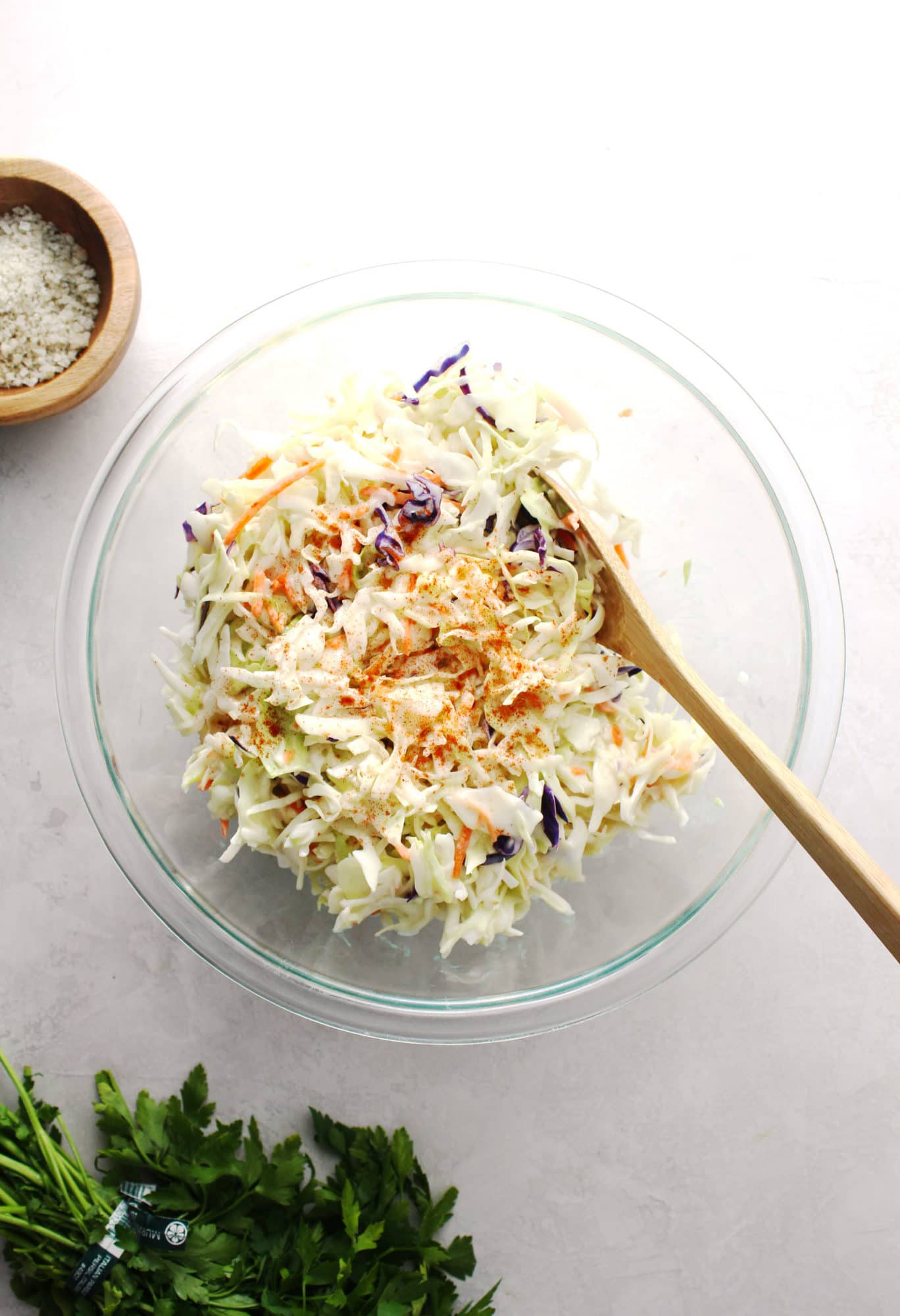coleslaw in a clear glass bowl with wooden spoon