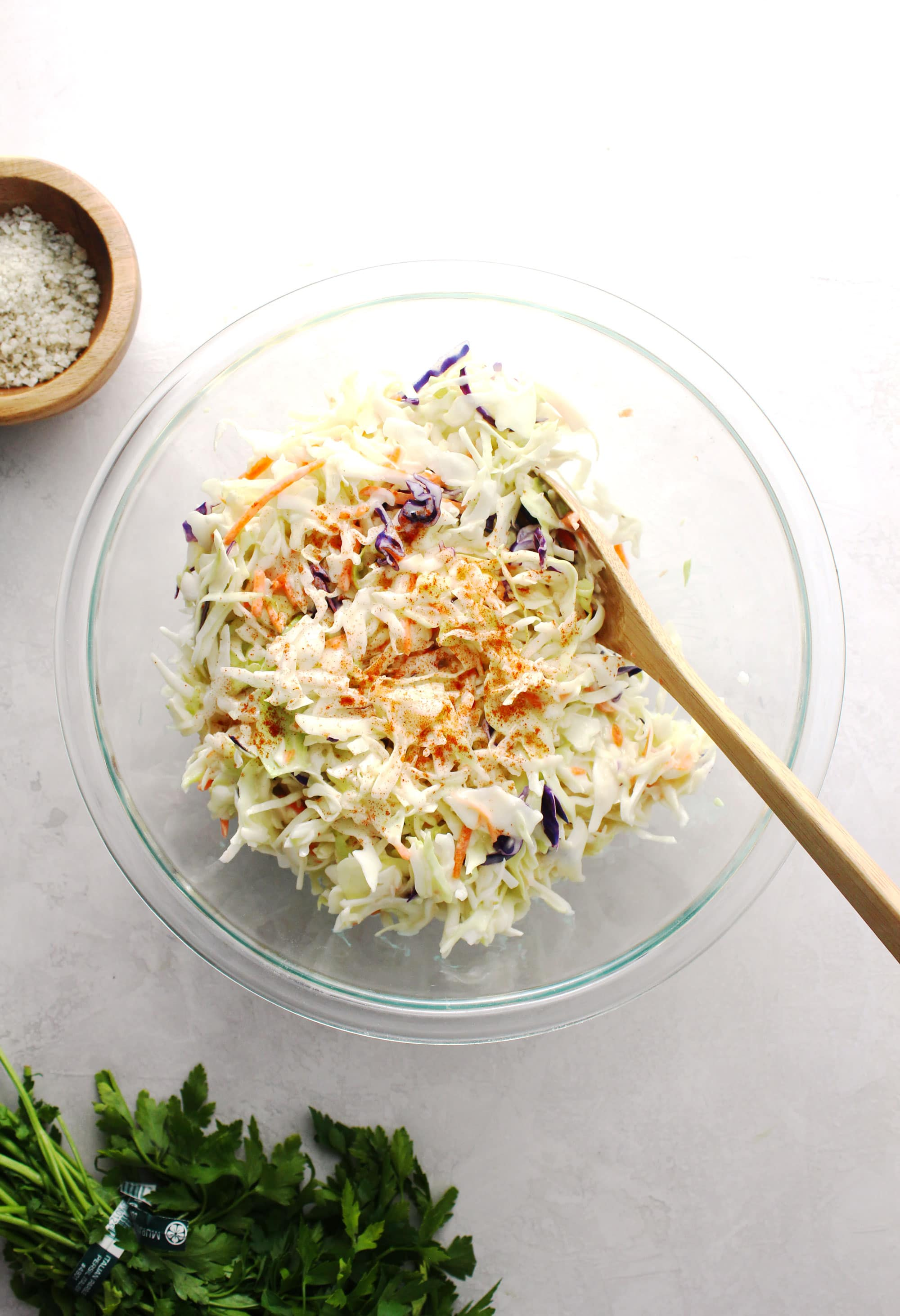 coleslaw in glass bowl with wooden spoon