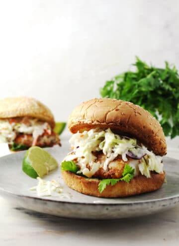 Close up of fish sandwich on a gray plate with lime wedge on the side.