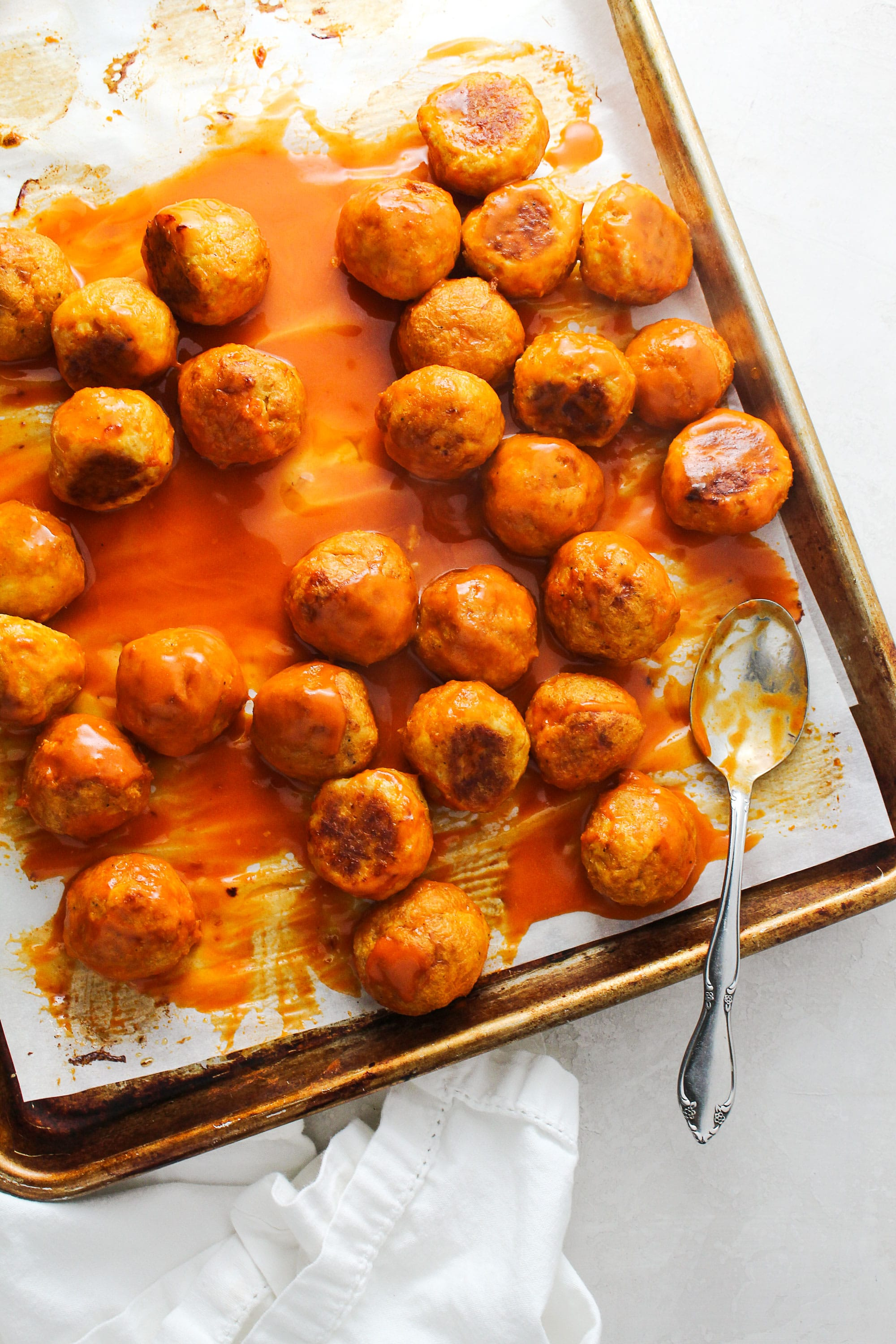 Buffalo Chicken Meatballs on a rimmed baking sheet with a silver spoon covered in sauce.