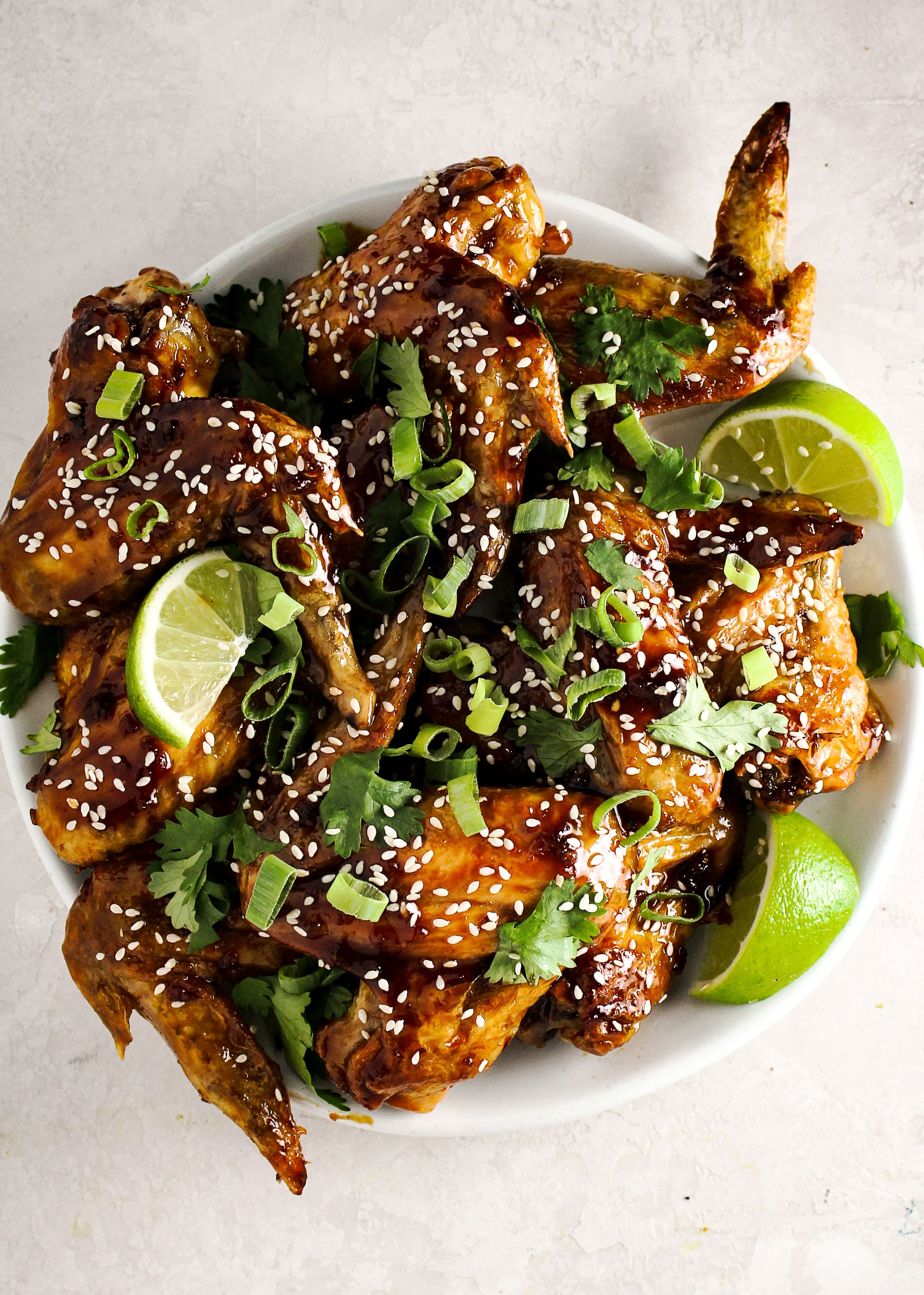 Crispy honey sriracha wings topped with green onions and sesame seeds.