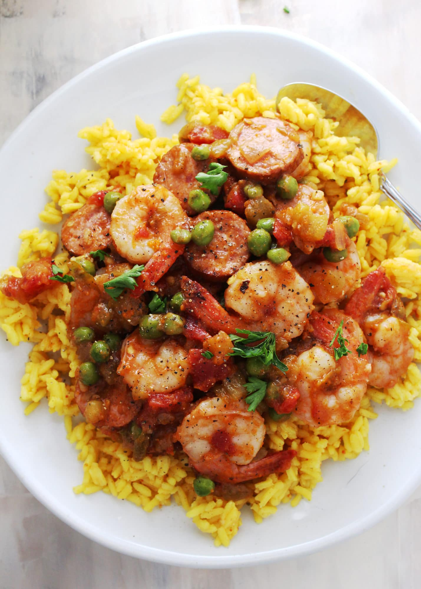 yellow rice topped with shrimp mixed with sausage and vegetables