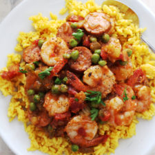 sausage and shrimp with yellow rice on a white plate