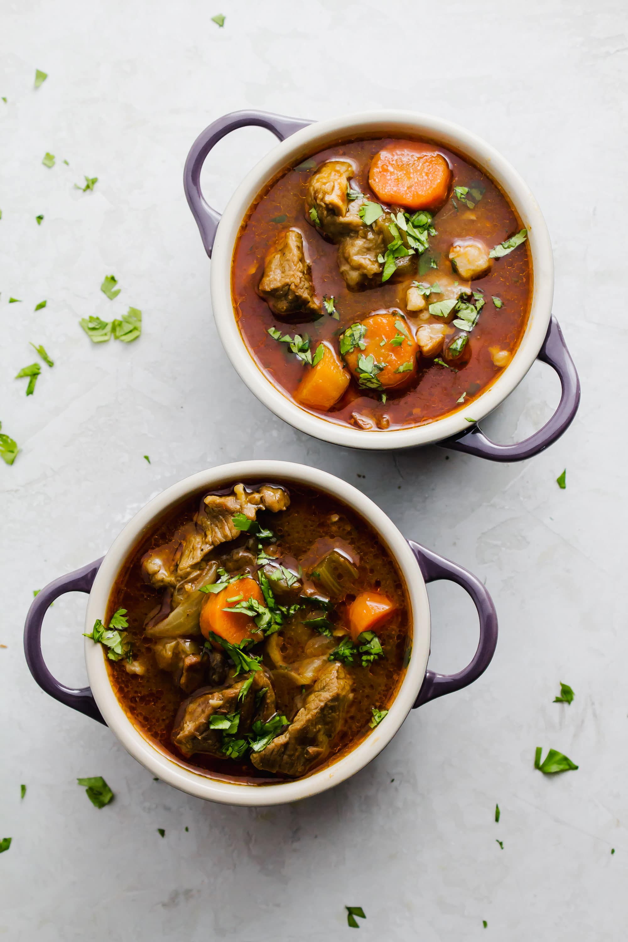 Stout beef stew in small purple soup bowls