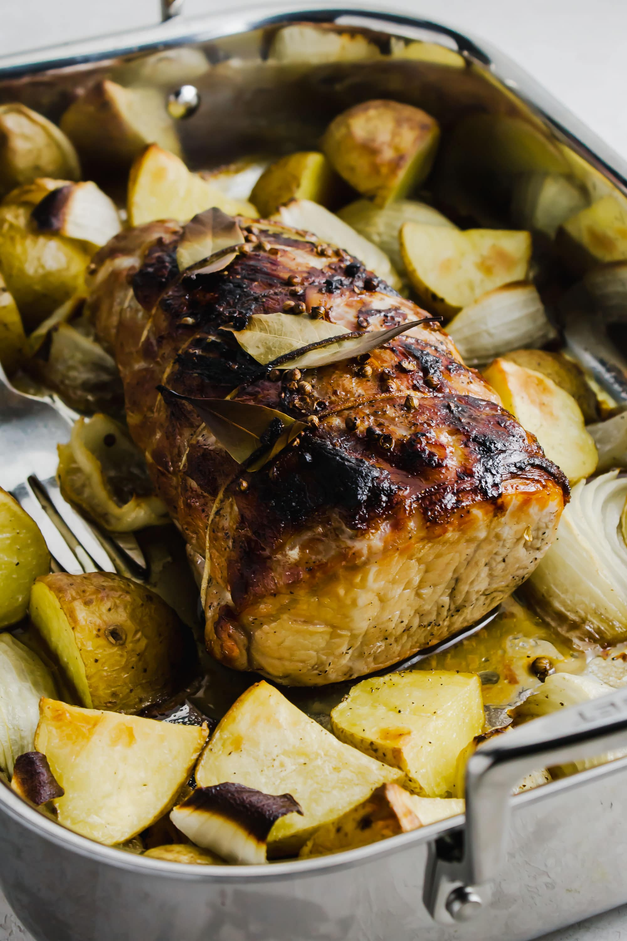 Cider brined pork roast with potatoes and onions surrounding it.