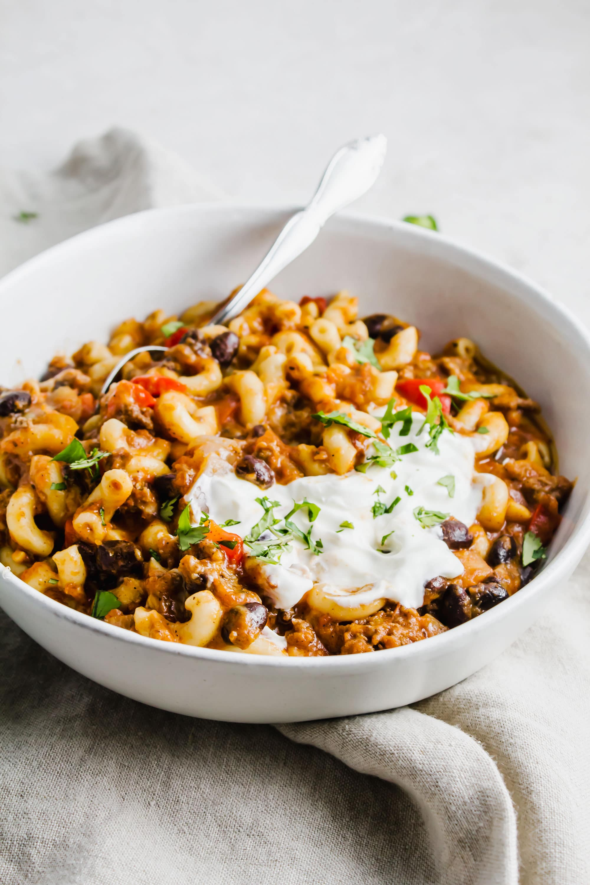 Instant pot chili mac and cheese in a bowl topped with sour cream and onions.