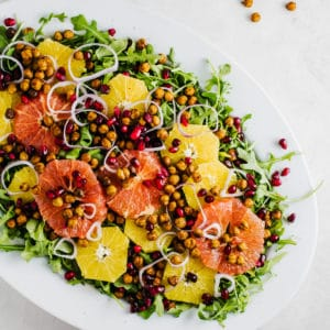 Winter citrus salad on a white plate with spicy chickpeas and pomegranate seeds.