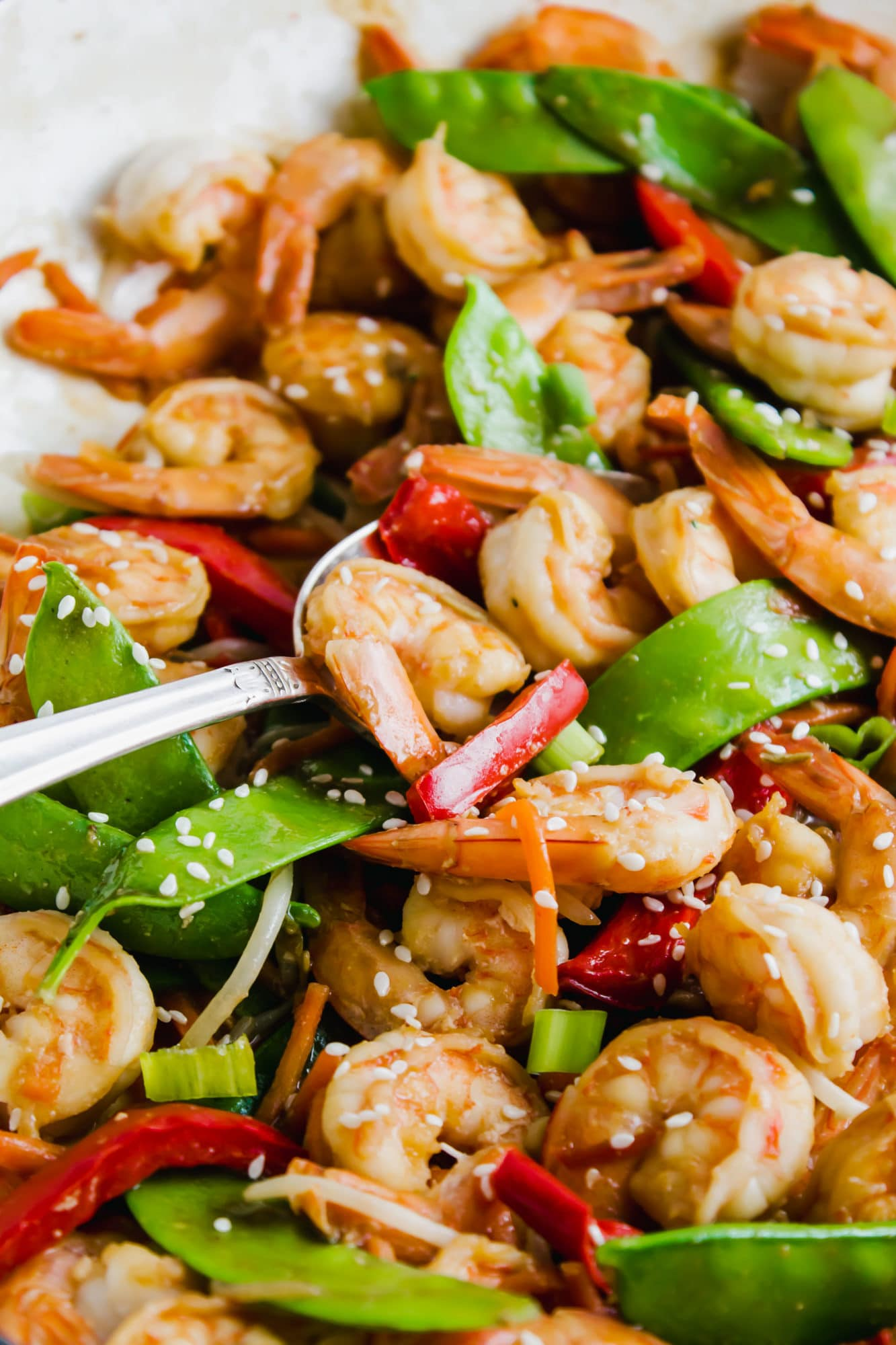 close up of shrimp stir-fry with silver spoon