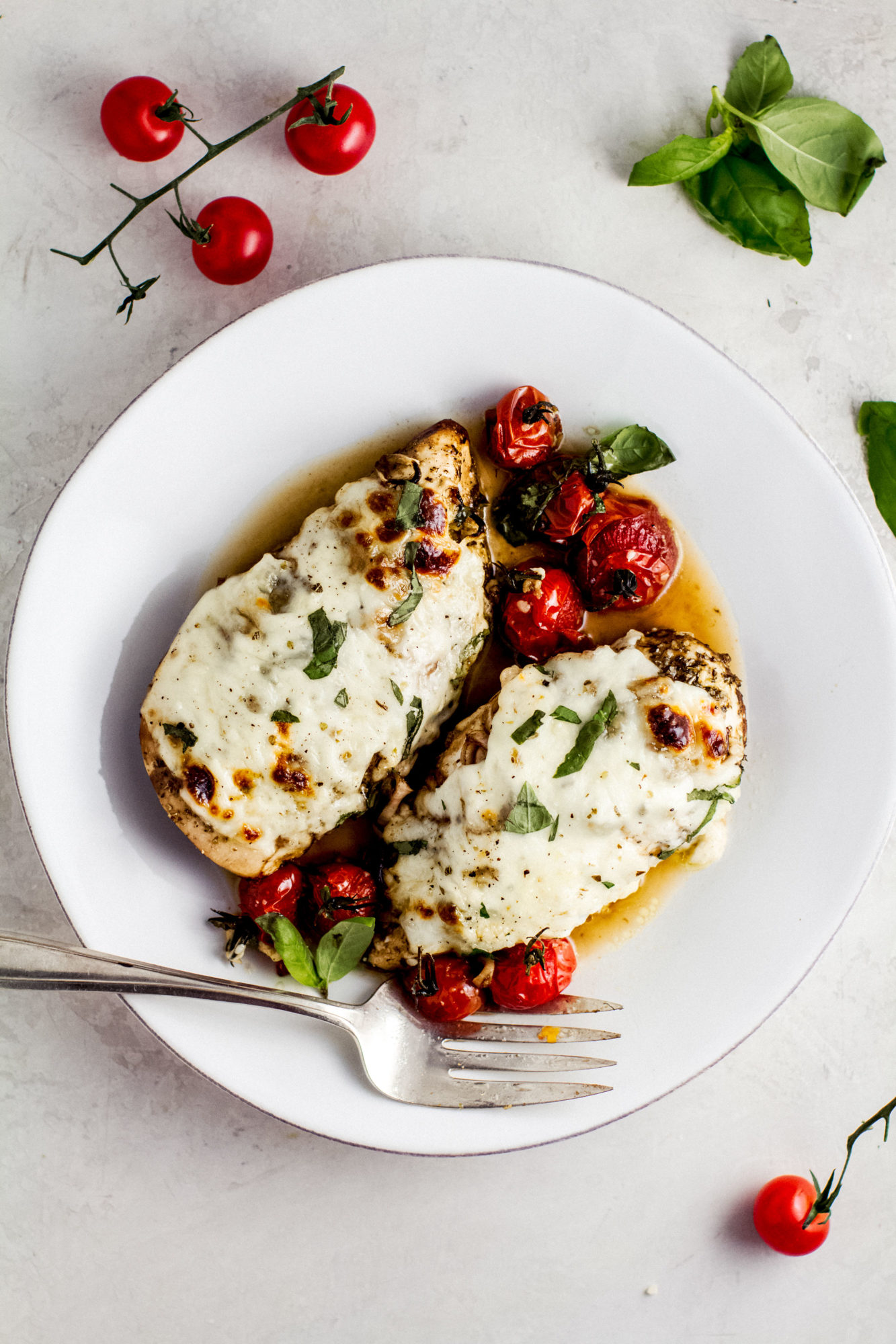 balsamic chicken covered in melted mozzarella on a white plate with silver serving fork