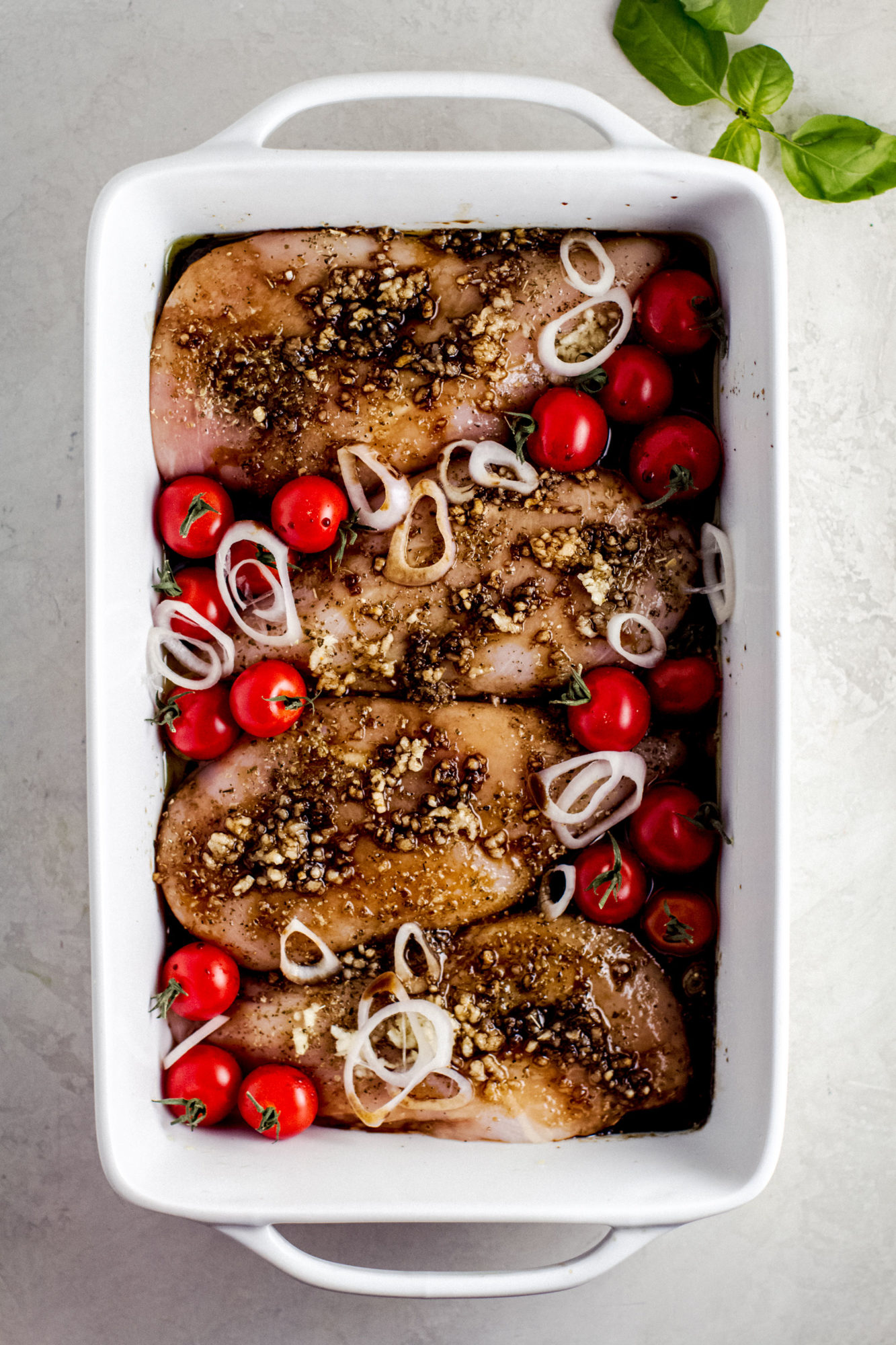 white baking dish with chicken breasts and ingredients for baked balsamic chicken