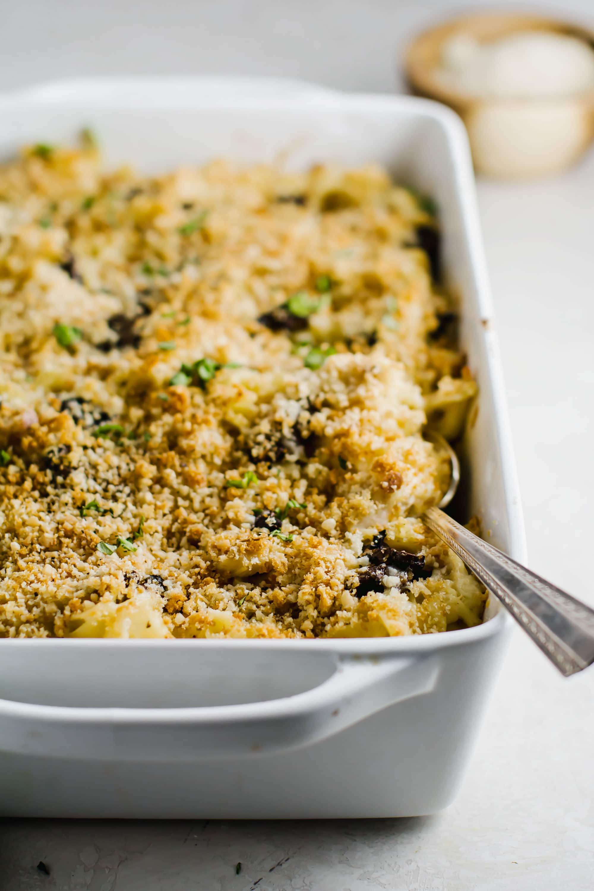 Chicken Tetrazzini in white casserole dish with silver spoon