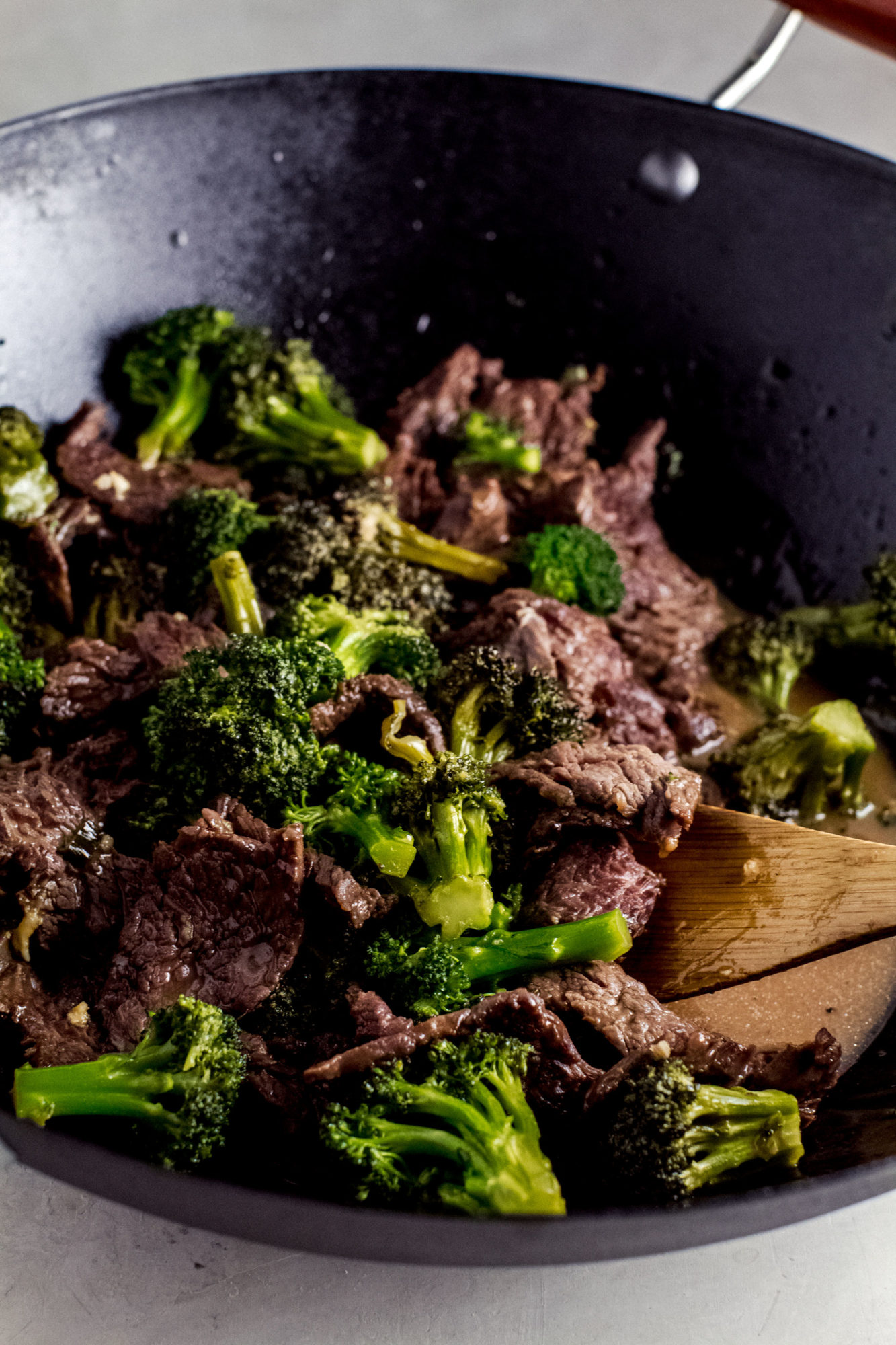 Beef and broccoli stir fry in a black wok.