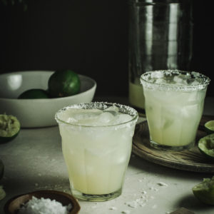 Margaritas in two glasses with salted rim and a bowl of limes behind.