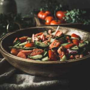 cucumber tomato salad in wooden bowl on top of cream colored table linen with fresh tomatoes in background