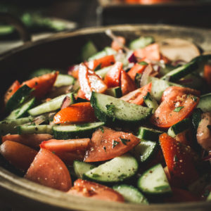 Italian cucumber, onion, and tomato salad in a large wooden bowl.