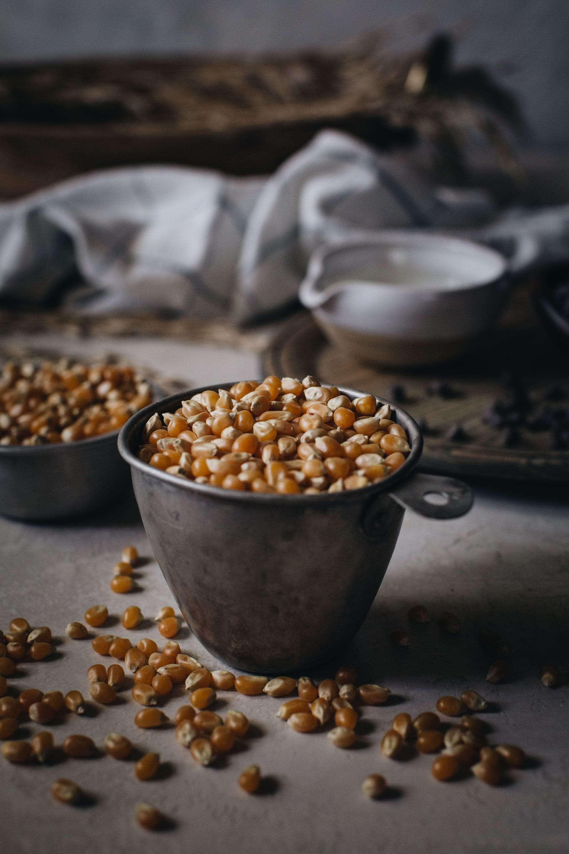 popcorn kernels in metal measuring cup