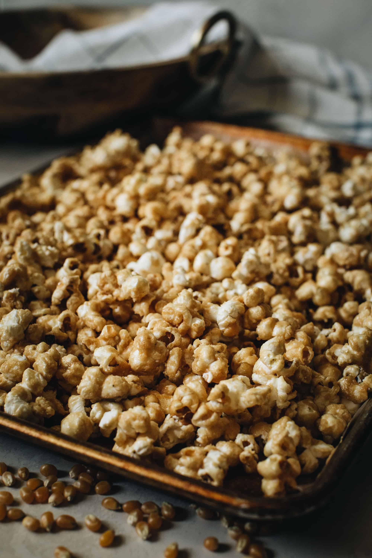caramel coated popcorn on rimmed baking sheet