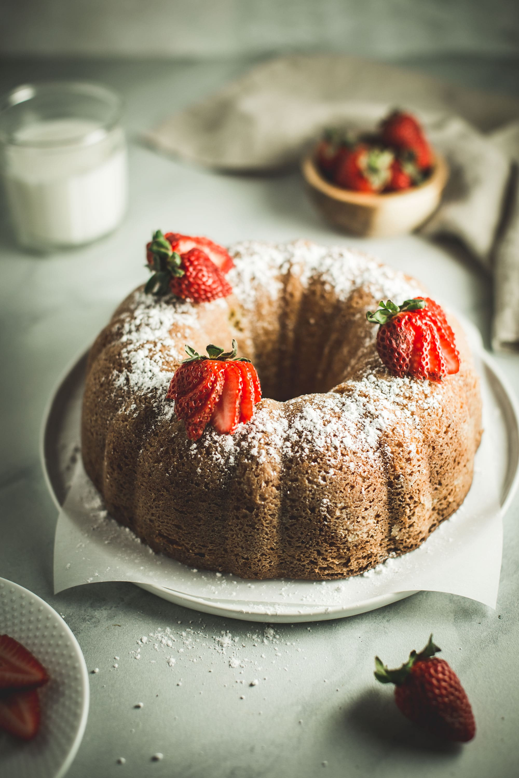 bundt cake covered in powdered sugar and topped with sliced strawberries