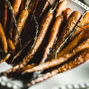 Cooked and roasted carrots on a white serving platter.