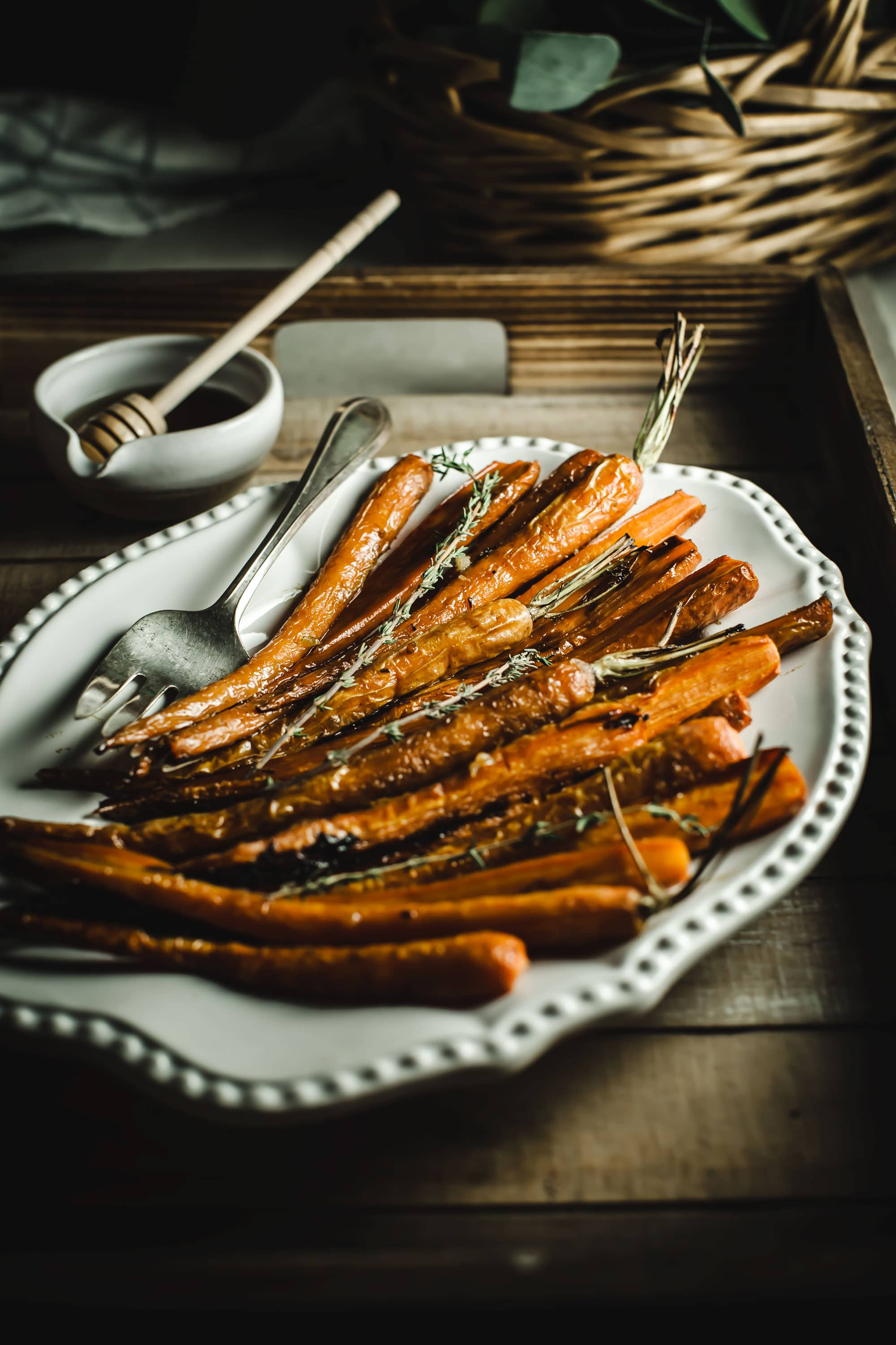 Carrots on a white serving platter sitting in a wooden tray with a bowl of honey behind it.