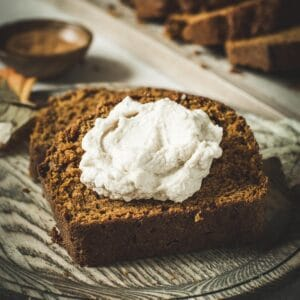 Moist pumpkin bread slice topped with whipped cream on a wooden plate.