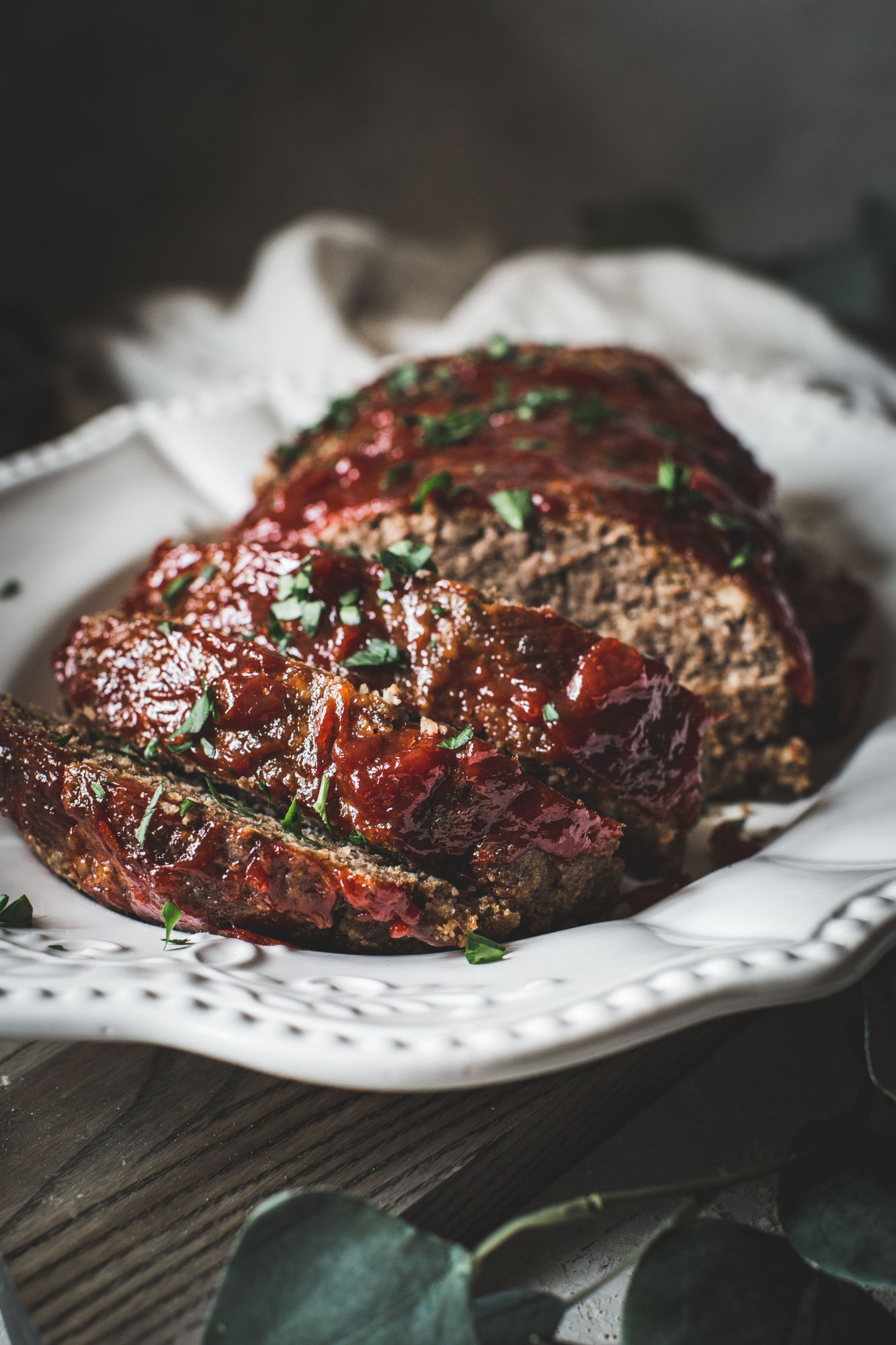 sliced classic meatloaf on white platter