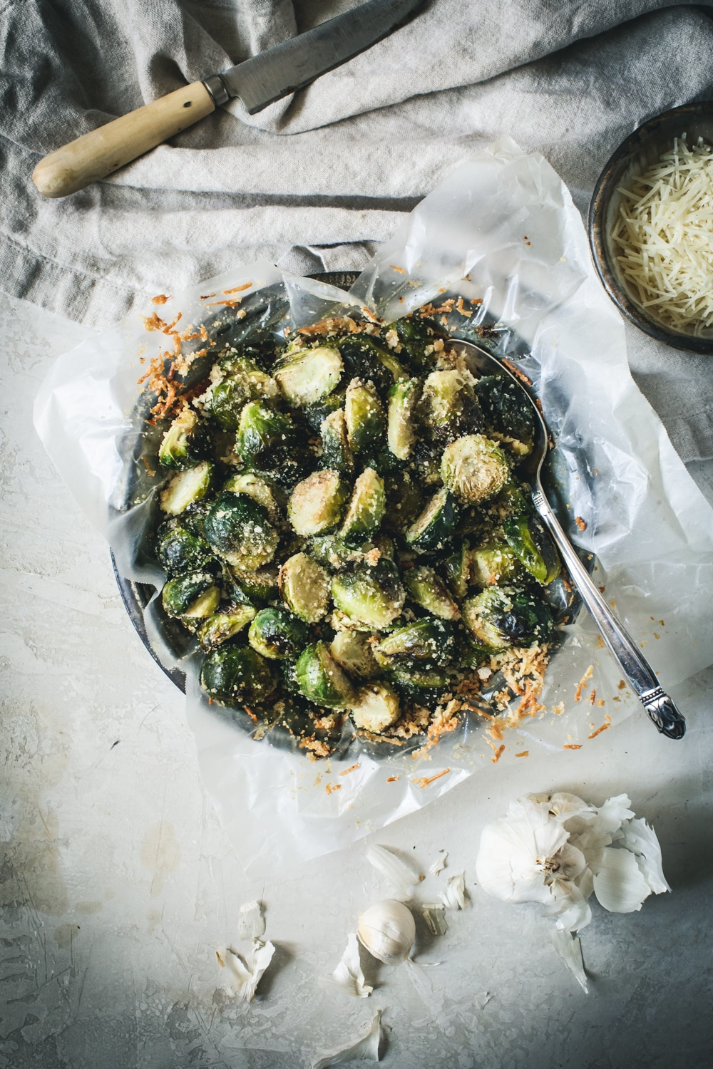 Brussel sprouts roasted and covered with shaved parmesan in a metal tin with silver serving spoon.